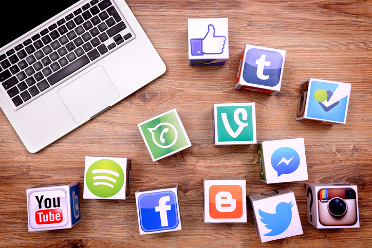?stanbul, Turkey - January 16, 2016: Paper cubes with Popular social media services icons, including Facebook, Instagram, Youtube, Twitter and a Macbook Pro laptop computer on a wooden desk.